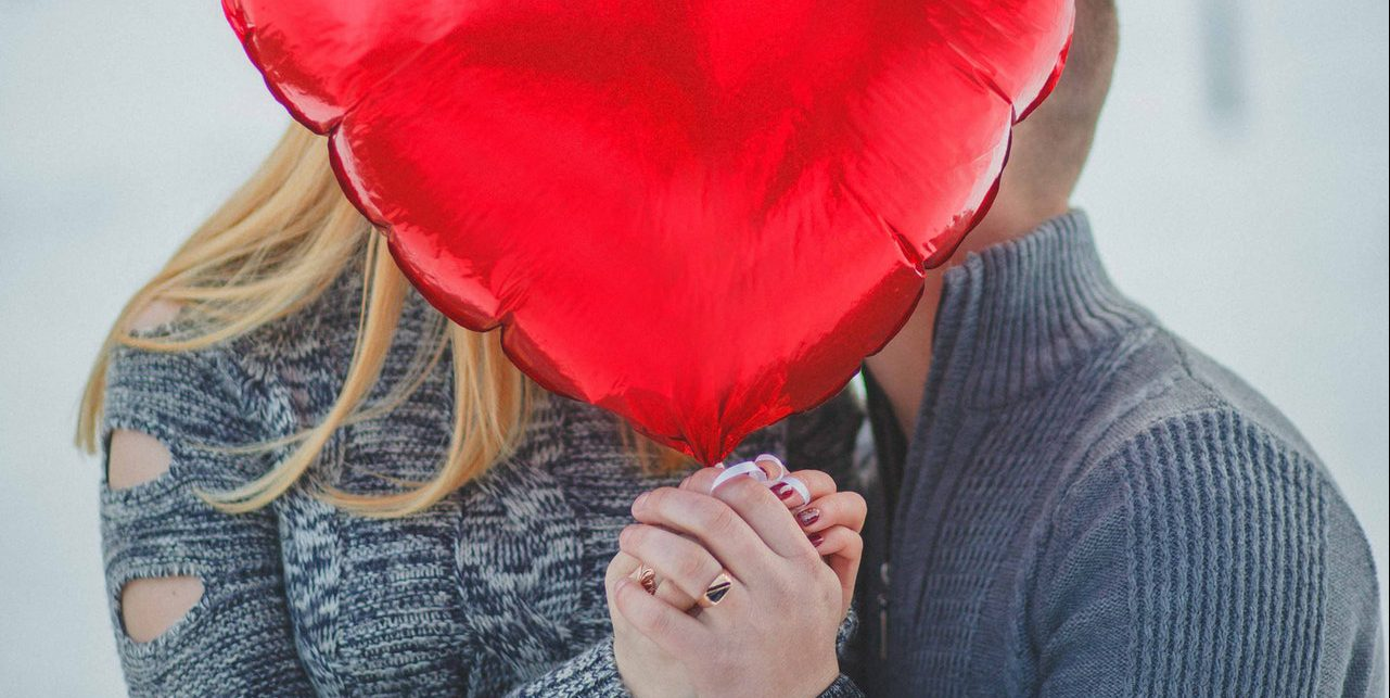 couple-holding-hands-with-red-heart-balloon